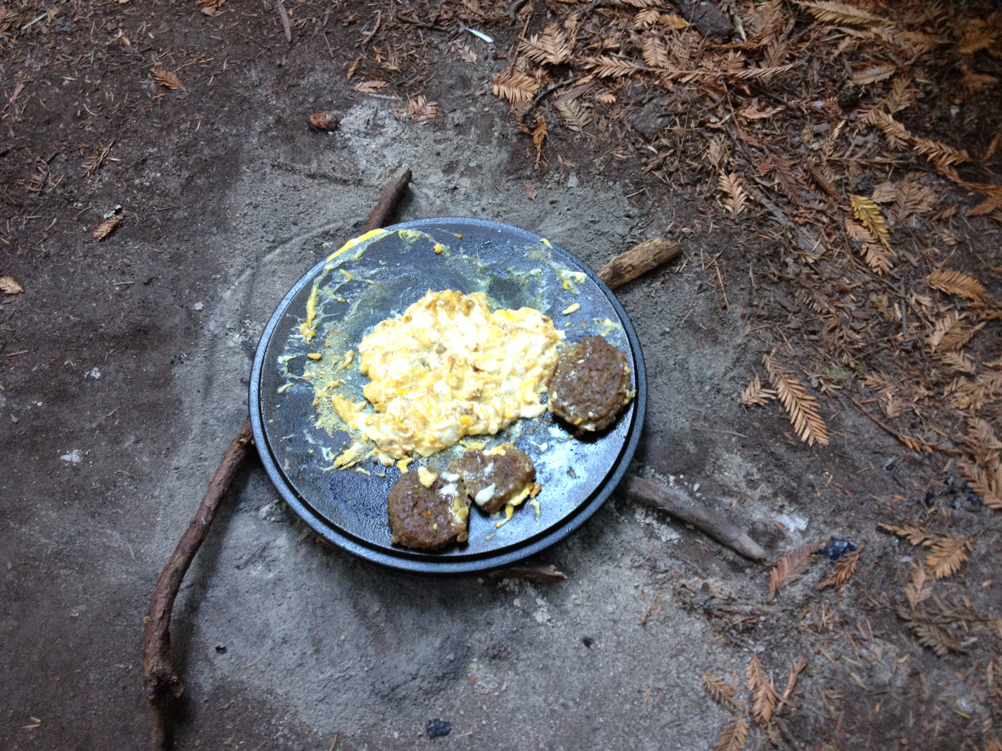 Cooking while camping. Dutch oven lid eggs and sausage.
